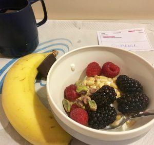Desayuno a base de plátano, yogur, bayas y pistachos