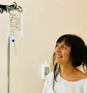 La autora en el hospital con su bata y su chute de glucosa en vena